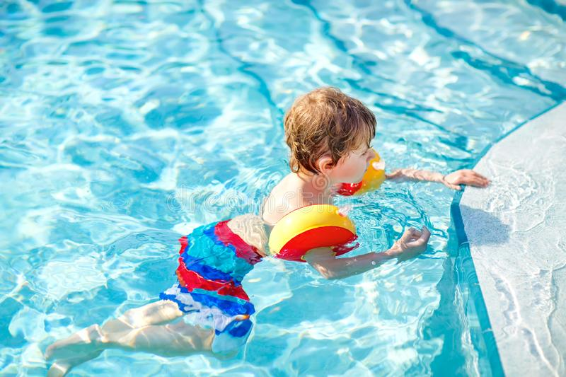 Happy little kid boy having fun in an swimming pool. Active happy child learning to swim. with safe floaties or swimmies. Family, vacations, summer concept royalty free stock photo