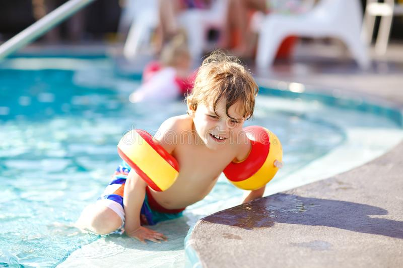 Happy little kid boy having fun in an swimming pool. Active happy child learning to swim. with safe floaties or swimmies. Family, vacations, summer concept royalty free stock images