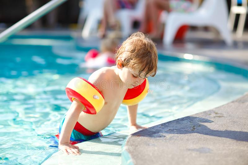 Happy little kid boy having fun in an swimming pool. Active happy healthy preschool child learning to swim. with safe. Floaties or swimmies. Family, vacations stock photos