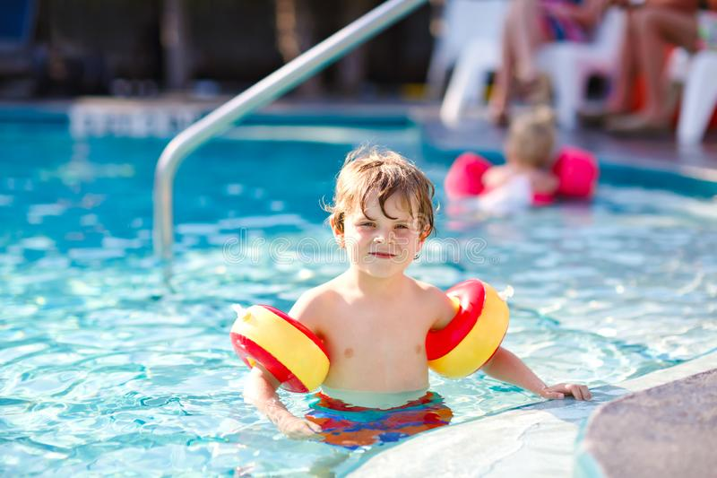 Happy little kid boy having fun in an swimming pool. Active happy healthy preschool child learning to swim. with safe. Floaties or swimmies. Family, vacations royalty free stock photo