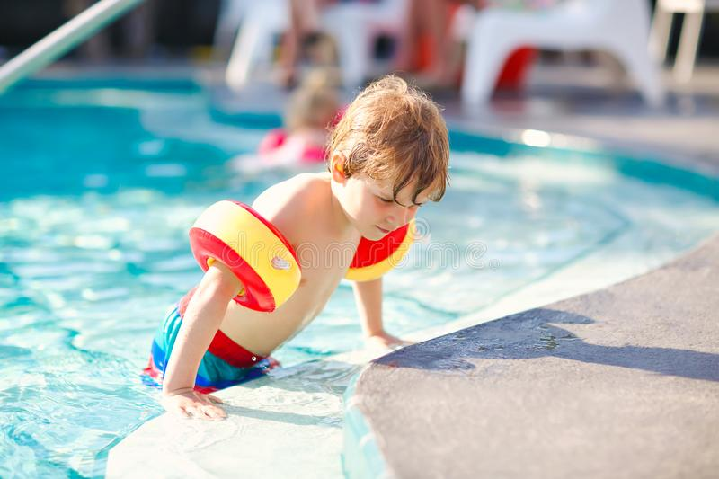 Happy little kid boy having fun in an swimming pool. Active happy healthy preschool child learning to swim. with safe. Floaties or swimmies. Family, vacations royalty free stock photos