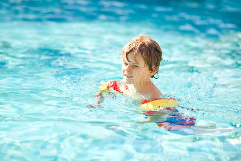 Happy little kid boy having fun in an swimming pool. Active happy healthy preschool child learning to swim. with safe. Floaties or swimmies. Family, vacations royalty free stock images