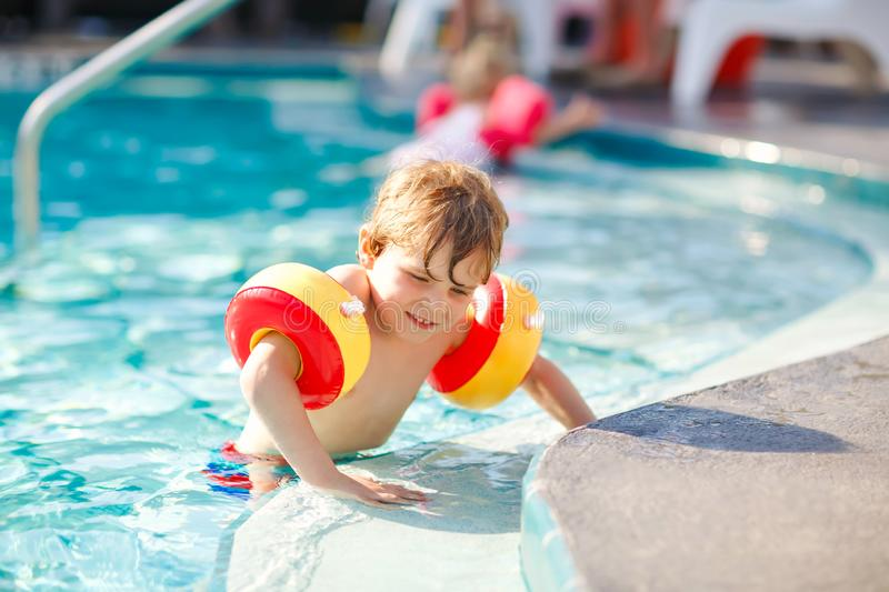 Happy little kid boy having fun in an swimming pool. Active happy healthy preschool child learning to swim. with safe. Floaties or swimmies. Family, vacations royalty free stock photography