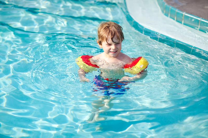 Happy little kid boy having fun in an swimming pool. Active happy preschool child learning to swim. with safe floaties. Or swimmies. Family, vacations, summer royalty free stock images