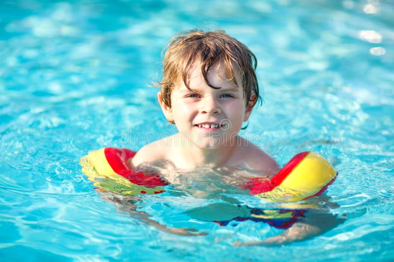 Happy little kid boy having fun in an swimming pool. Active happy preschool child learning to swim. with safe floaties. Or swimmies. Family, vacations, summer royalty free stock image
