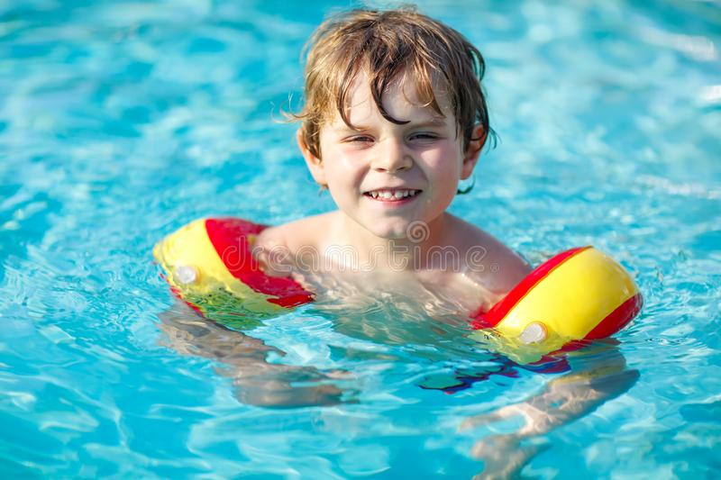 Happy little kid boy having fun in an swimming pool. Active happy preschool child learning to swim. with safe floaties. Or swimmies. Family, vacations, summer stock image