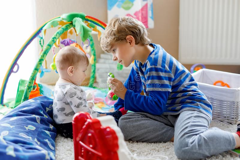 Happy little kid boy with newborn baby girl, cute sister. Siblings. Brother and baby playing together. Older child. Showing baby crawling. Family and love royalty free stock images