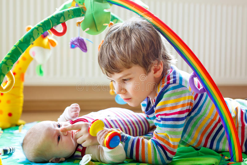 Happy little kid boy with newborn baby sister girl. Happy little kid boy with newborn baby girl, cute sister. Siblings. Brother and baby playing with colorful royalty free stock photo
