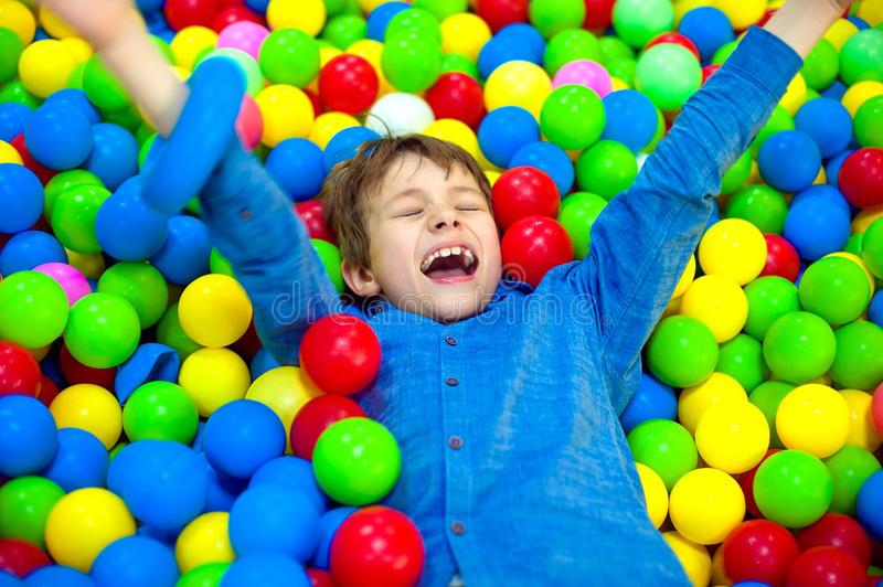 Happy little kid boy playing at colorful plastic balls playground high view. Funny child having fun indoors. royalty free stock photography