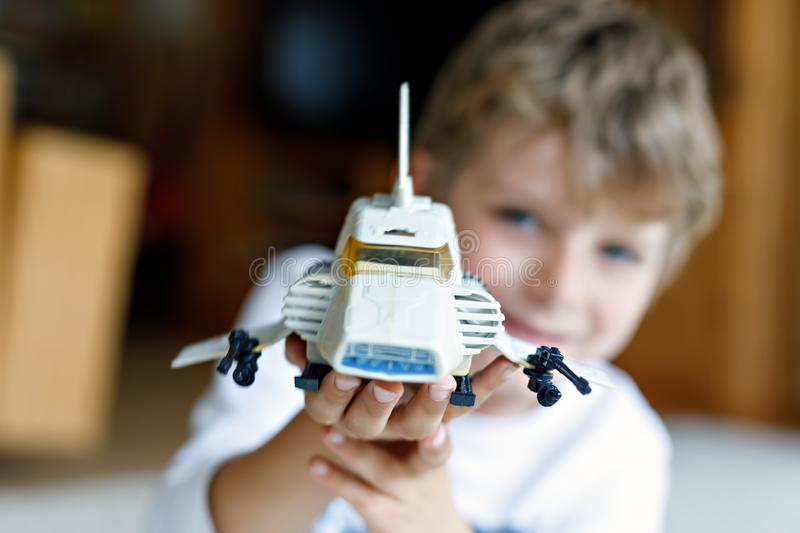Happy little kid boy playing with space shuttle toy. Cute child in having fun in the morning before school. Selective. Focus on old plastic toy. Blond kid on stock photos