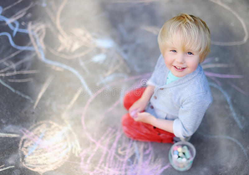 Happy little kid boy sitting and drawing with colored chalk on asphalt royalty free stock image
