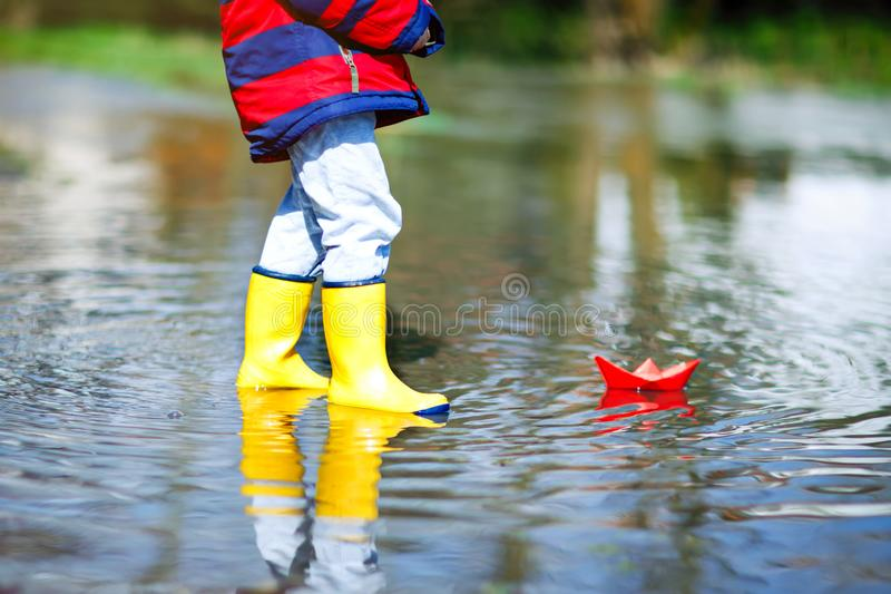 Happy little kid boy in yellow rain boots playing with paper ship boat by huge puddle on spring or autumn day royalty free stock images