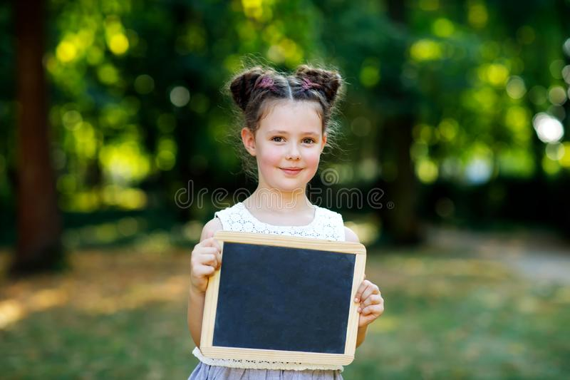 Happy little kid girl holding empty chalk desk in hands. Schoolkid on first day of elementary class. Healthy adorable royalty free stock image