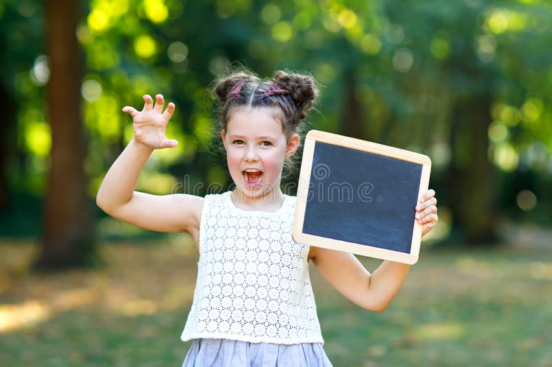 Happy little kid girl holding empty chalk desk in hands. Schoolkid on first day of elementary class. Healthy adorable royalty free stock photo