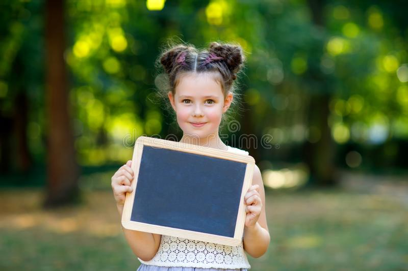 Happy little kid girl holding empty chalk desk in hands. Schoolkid on first day of elementary class. Healthy adorable stock image
