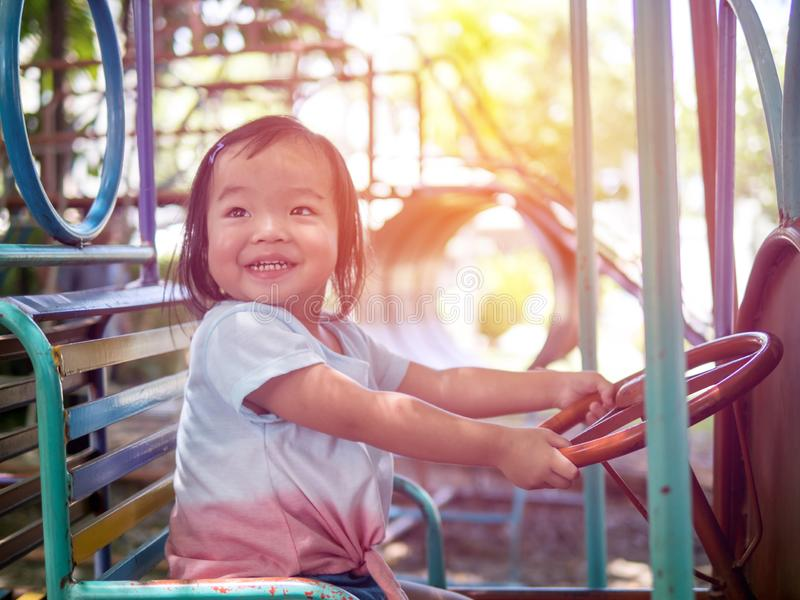 Happy little kid girl playing on merry-go-round in the park on a very sunny day. Adorable children spending happy time royalty free stock photo