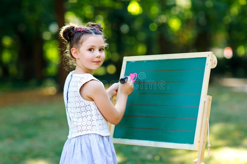 Happy little kid girl standing by big chalk desk Preschool or schoolkid on first day of elementary class. Back to school stock images