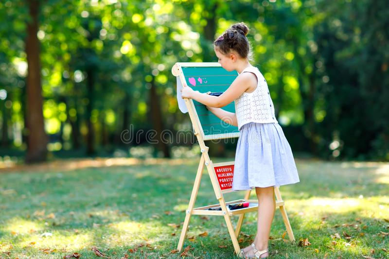 Happy little kid girl standing by big chalk desk Preschool or schoolkid on first day of elementary class. Back to school royalty free stock photography