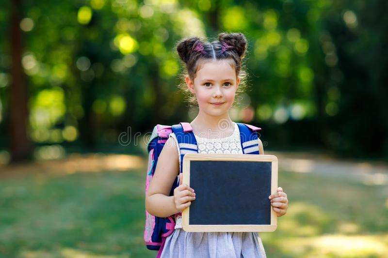 Happy little kid girl standing with desk and backpack or satchel. Schoolkid on first day of elementary class. Healthy stock photo