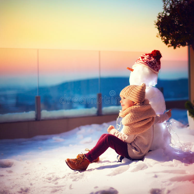 Happy little kid and his friend snowman watching the sun goes down sitting in snow on rooftop terrace in one winter evening stock photo