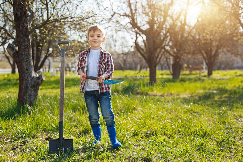 Happy little kid posing for picture in garden stock photos