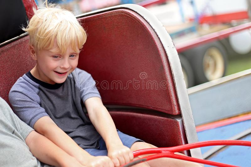 Happy Little Kid Riding Tilt-a-whirl Carnvial Ride. A happy little kids is smiling as he spins in circles on a tilt-a-whirl carnival ride stock photo