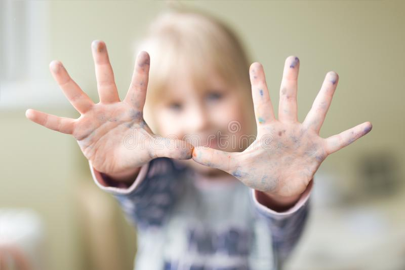 Happy little kid showing hands dirty with paint. Enjoying art and painting concept royalty free stock images