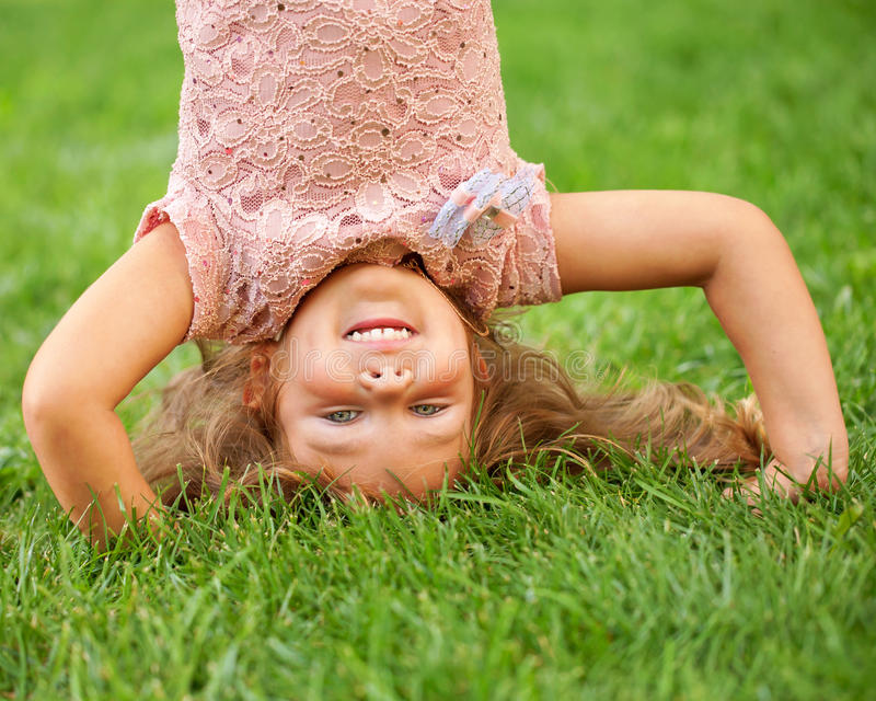 Happy little kid standing on his head royalty free stock image
