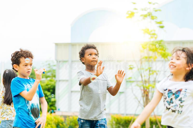 Happy little kids blowing soap bubbles in summer park. Kid and friends in international preschool play a bubble. royalty free stock image