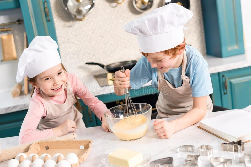 Happy little kids in chef hats and aprons whisking dough. In kitchen royalty free stock photo