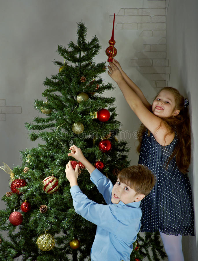 Happy little kids decorate Christmas tree. In beautiful living room with traditional fire place royalty free stock image