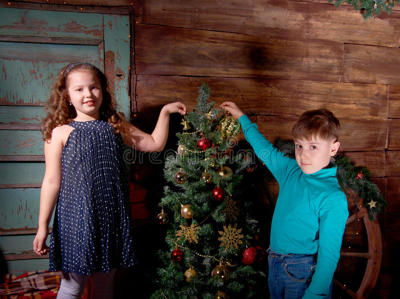 Happy little kids decorate Christmas tree. In beautiful living room with traditional fire place royalty free stock photos