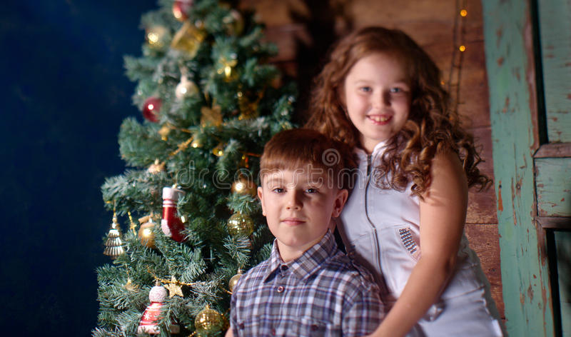 Happy little kids decorate Christmas tree. In beautiful living room with traditional fire place stock photos