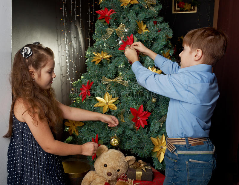 Happy little kids decorate Christmas. Tree in beautiful living room with traditional fire place stock image
