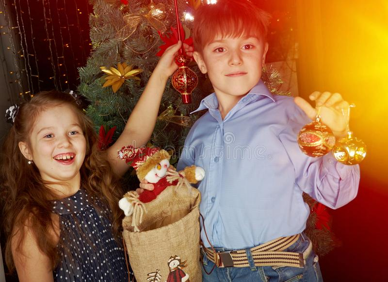 Little kids decorate Christmas. Happy little kids decorate Christmas tree in beautiful living room with traditional fire place stock image
