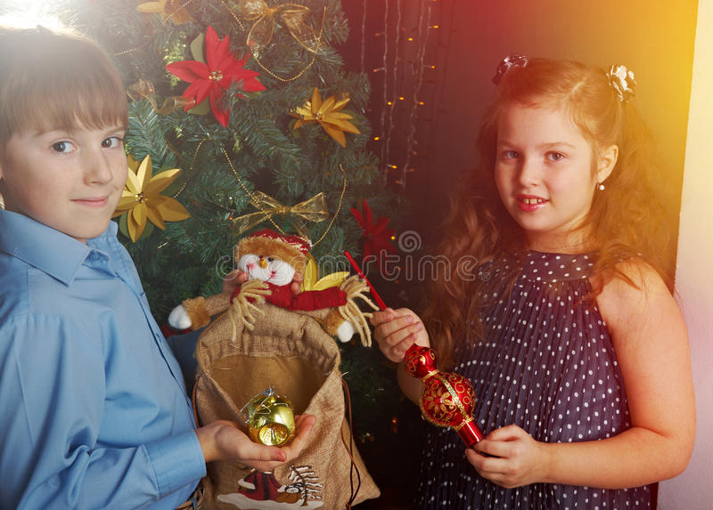 Happy little kids decorate Christmas tree. In beautiful living room with traditional fire place royalty free stock images