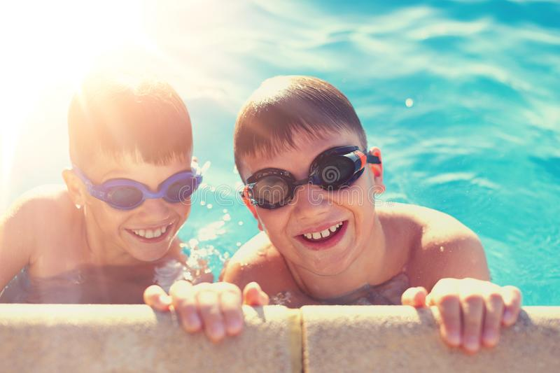Happy little kids have fun at side of swimming pool royalty free stock image