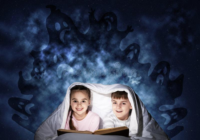 Happy little kids reading book in bed royalty free stock photos