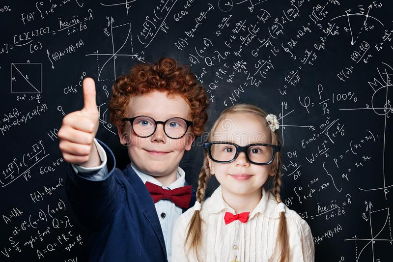 Happy little kids in school uniform having fun on blackboard background with science formulas, back to school concept royalty free stock photo
