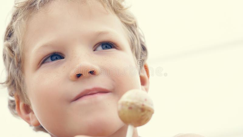 Happy little preschool boy with candy lollypop at summer beach, outdoors. stock photo