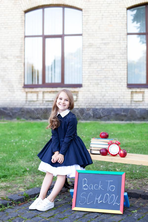 Happy little preschool child girl in a vintage dress with books, apples on her first day to school or kindergarten. Healthy child royalty free stock photo