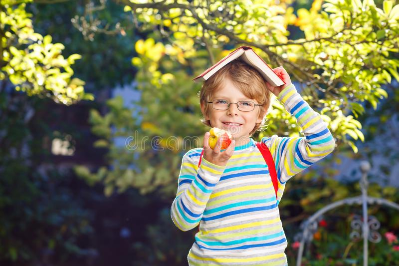 Happy little preschool kid boy with glasses, books, apple and backpack on his first day to school or nursery. Funny stock photos