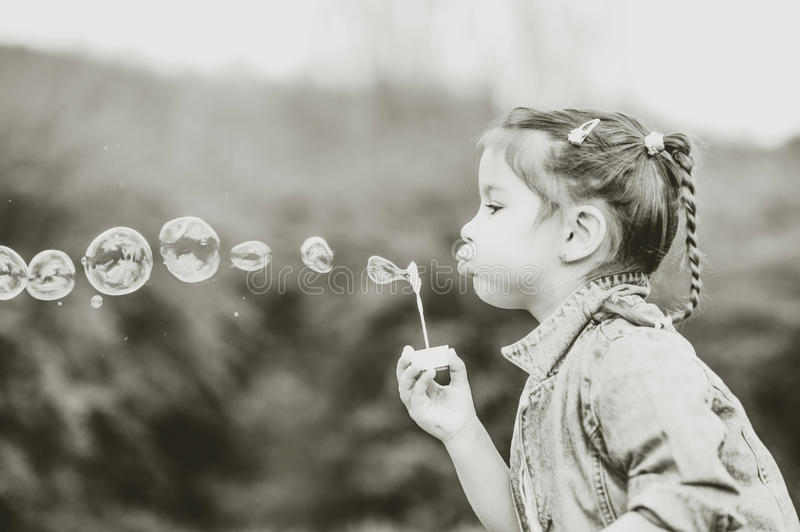 Happy little pretty girl outdoor in the park blowing bubbles stock photos