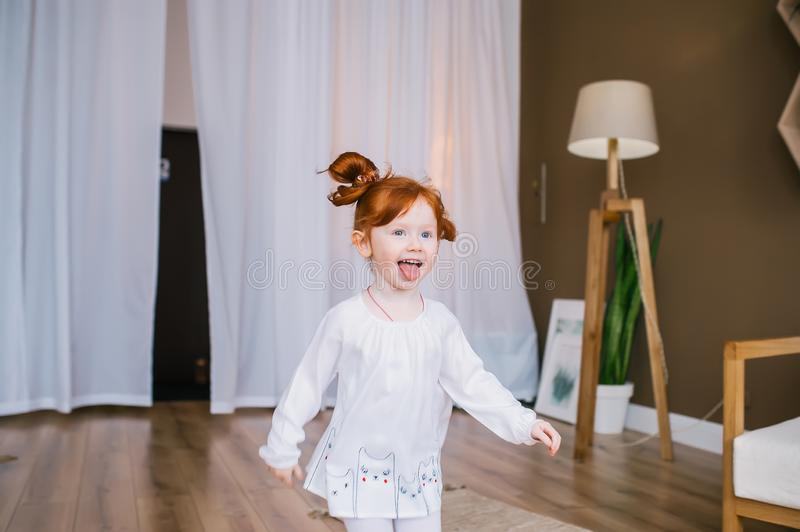 Happy little redhead girl playing in big room stock photography