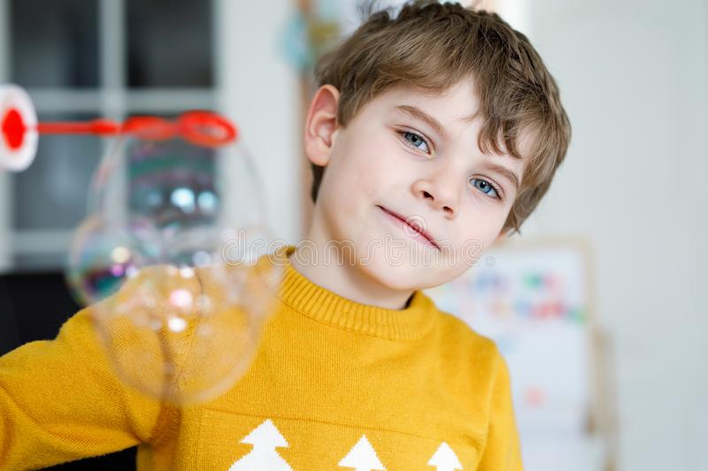 Happy little school boy playing with soap bubbles at home. Kid having fun. stock photos