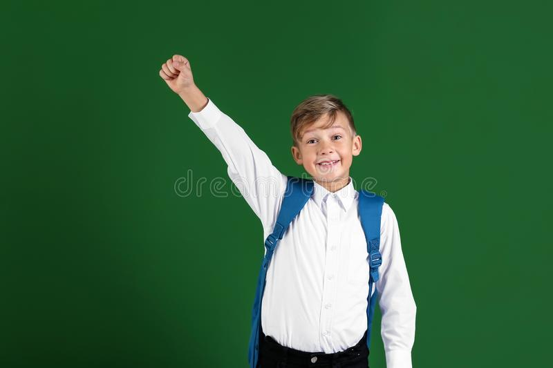 Happy little schoolboy with backpack on color background stock photo