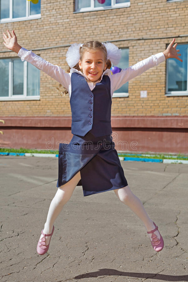 Happy little schoolgirl jumping. Raising his hands up stock images