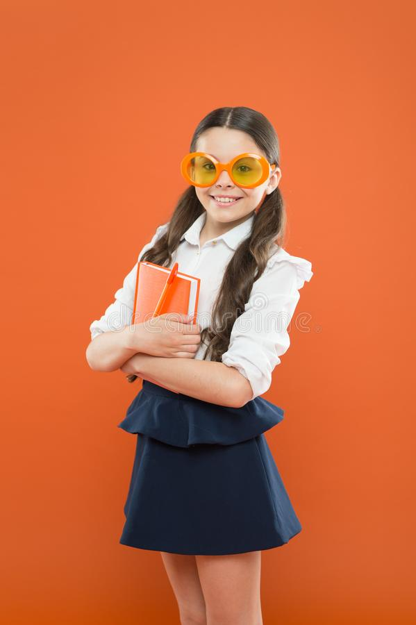 Happy little schoolgirl ready for lesson. Cute child with book. Study foreign language. Study literature. Pupil likes. Study. The more you know the more you stock image