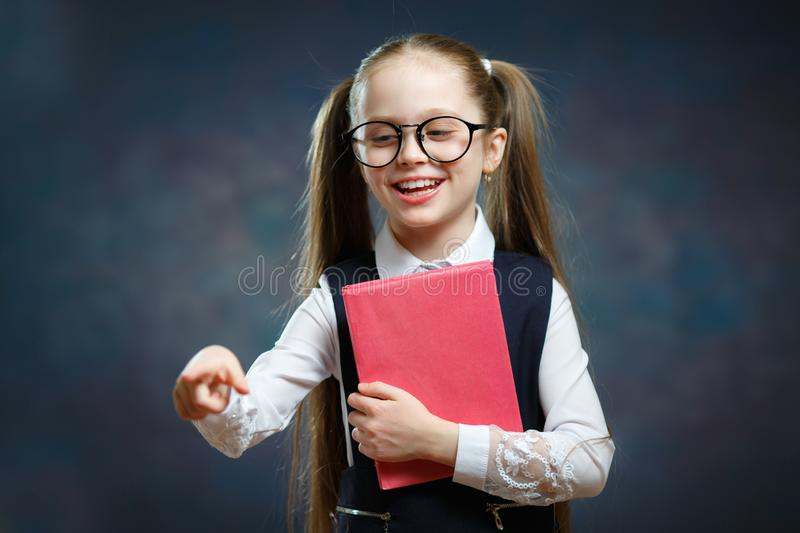 Happy Little Schoolgirl in Uniform Hold Book Tight royalty free stock photo