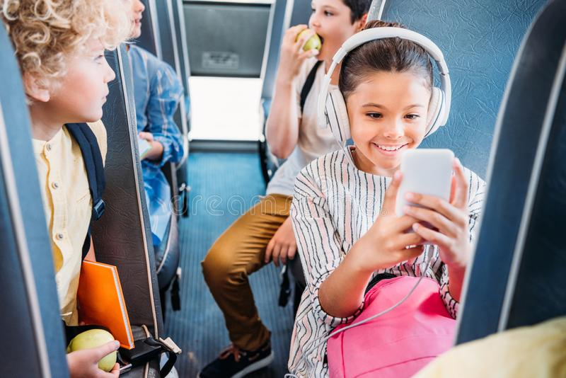 happy little schoolgirl using smartphone and listening music with headphones while riding on school bus royalty free stock images